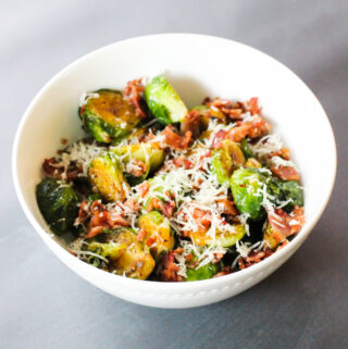 A white china bowl filled with fried Brussels sprouts. The sprouts are topped with crumbled bacon bits and freshly grated parmesan cheese. Background is a gray countertop.