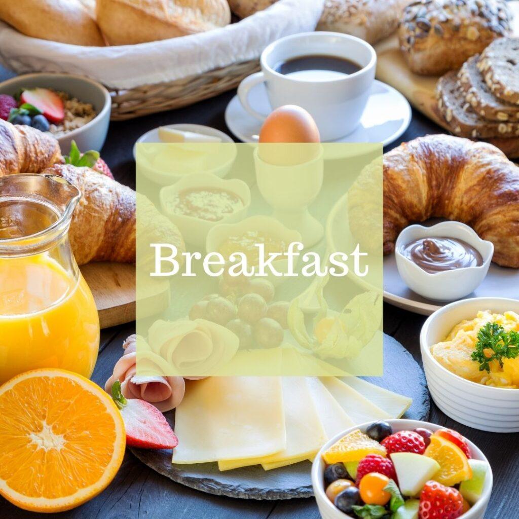 A breakfast spread of fruit, croissants, eggs, orange juice, and coffee.