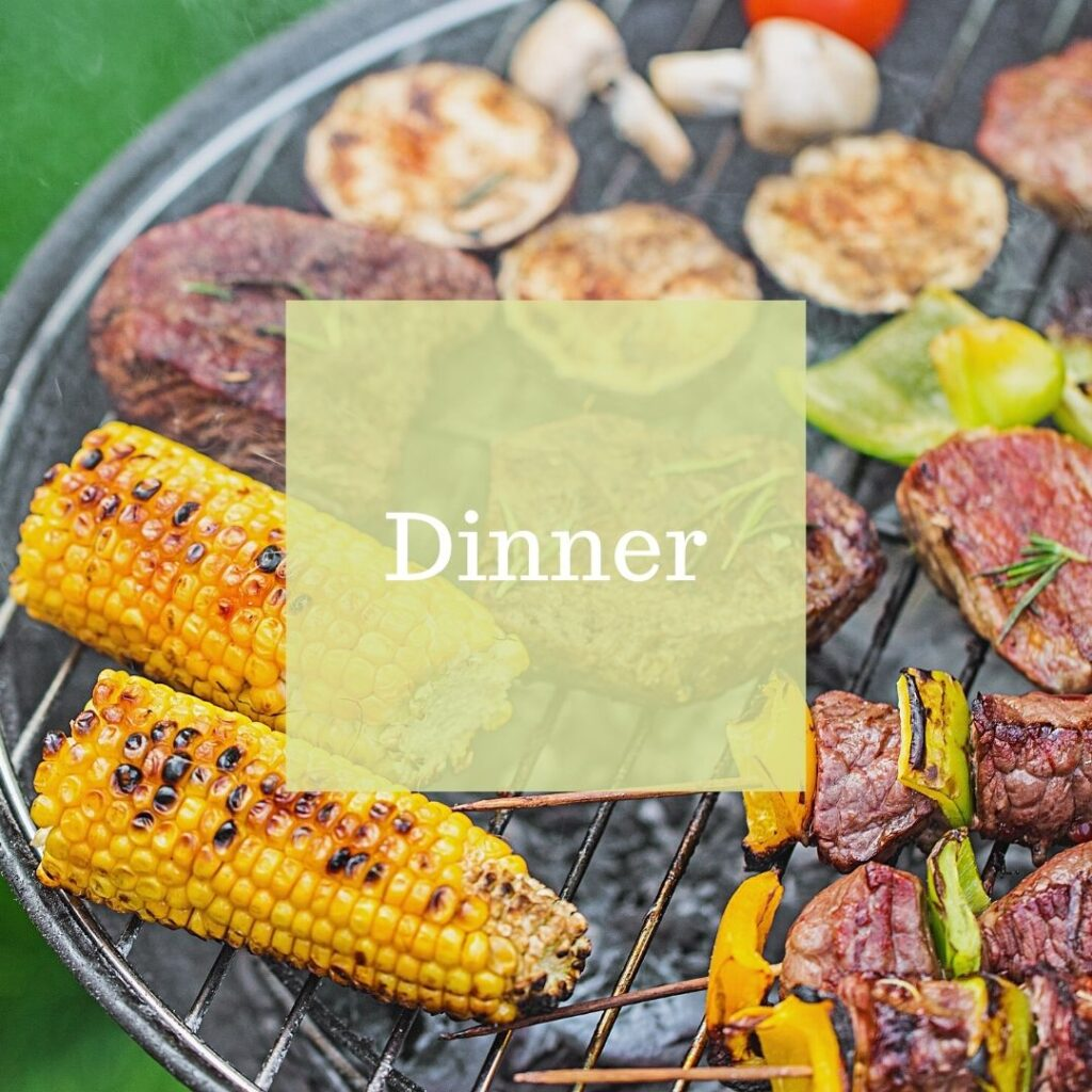Dinner cooking on a charcoal grill. Corn on the cob, mushrooms, and shish kabobs.